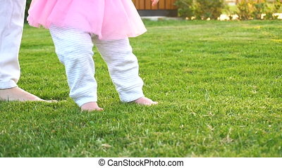 Baby girl doing first steps with mothers help - Little baby...