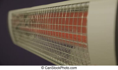 Electric infrared heater warms up and starts to glow