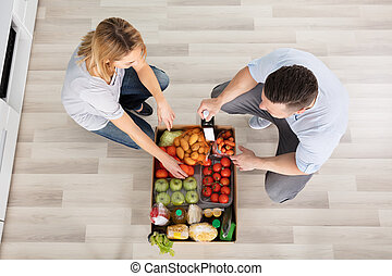 Couple With Groceries In The Cardboard Box