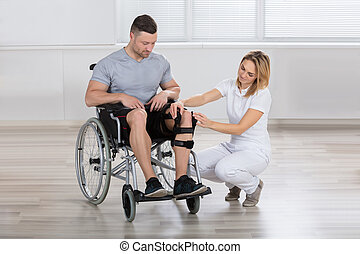 Female Physiotherapist Fixing Knee Braces On Man's Leg -...