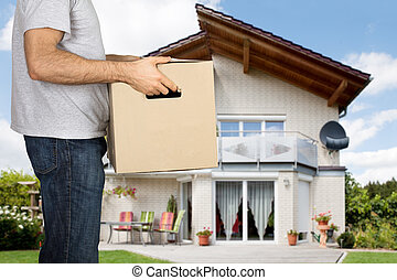 Man Holding Cardboard Box In Front Of His House