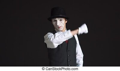 Man mime cleaning glass on a black background. It splatters the windshield wiper and wipes his sleeve