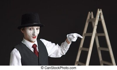 Man nime standing at the ladder on a black background. Showing thumbs up and thumbs down. The concept of career, business