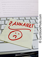 note on computer keyboard: dentist - a memo is on the...