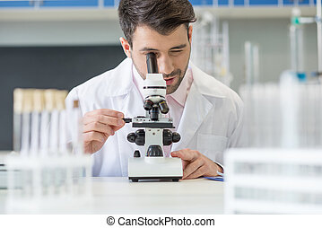Man scientist in white coat working with microscope in lab