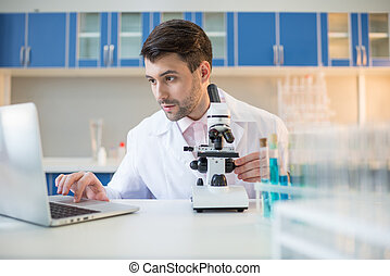 Man scientist in lab coat working with microscope and laptop