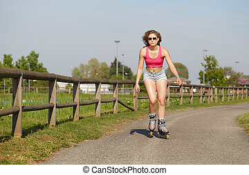 Skating woman on rollerblades in park.