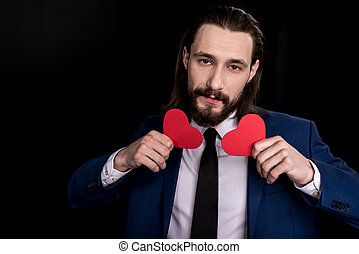 Man holding paper hearts - Handsome bearded man holding red...