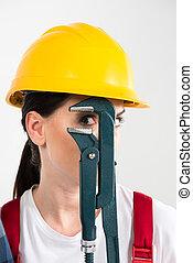 Female builder holding wrench - Portrait of female builder...