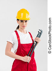 Female builder holding wrench - Attractive female builder in...
