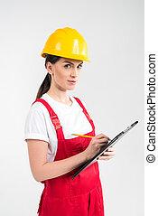 Female engineer in helmet writing in clipboard and looking...