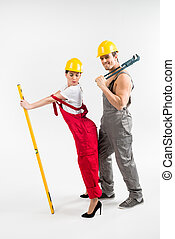 Male and female builders posing - Young male and female...