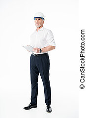 Mature male architect in hard hat using digital tablet