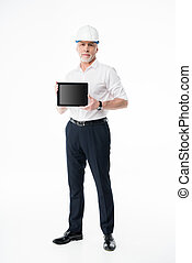 Mature male architect in hard hat showing digital tablet