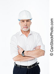 Mature male architect in hard hat with arms crossed