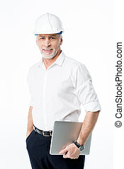Mature male architect in hard hat holding digital tablet and...