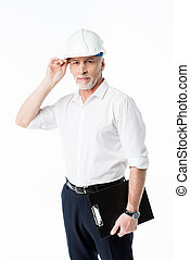 Mature male architect in hard hat holding clipboard and...
