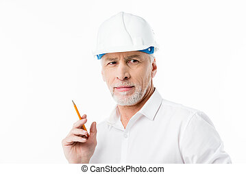 Mature male architect in hard hat holding pencil on white