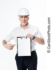 Mature male architect in hard hat holding blank clipboard