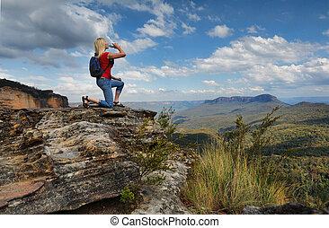 Woman drinking water on mountain summit Australia - Female...