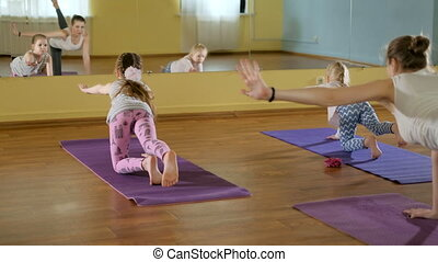 mother and daughtersr doing yoga together in a fitness...