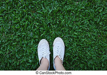 Selfie of feet in sneakers shoes on green grass background with copy space, spring and summer concept