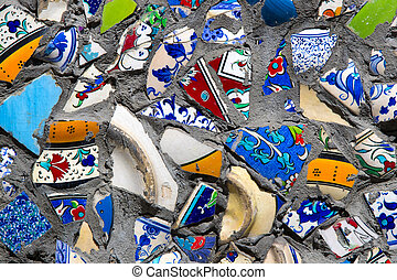 Wall with broken ceramic plates colored fragments