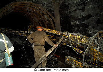 miner works in a mine with coal shearer