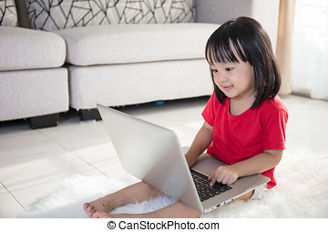 Asian Chinese little girl playing laptop - Asian Chinese...