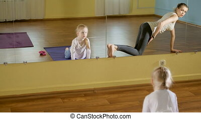 mother and daughtersr doing yoga together in a fitness studio