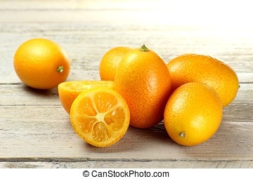 kumquats on wooden background