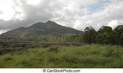 Driving a bike past volcano Batur. Panorama view from...