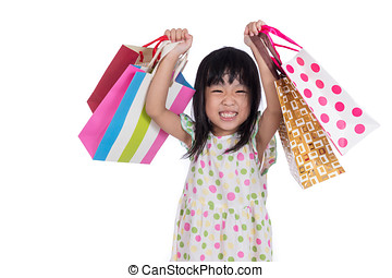 Asian chinese little girl with shopping bags in isolated...