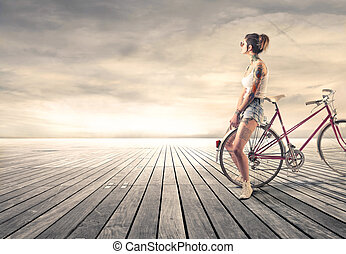 Woman at sunset - Woman with bike at sunset