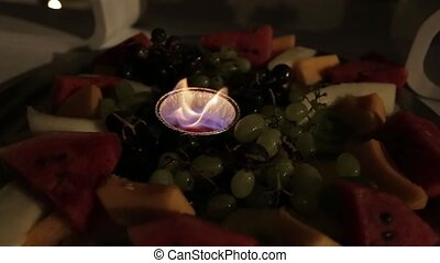 Wedding decorations, a candle lit among fruits.