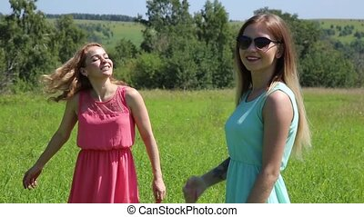 young girls spinning on a green grass, girlfrend in nature