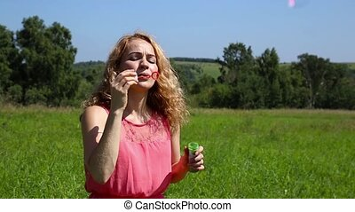 beautiful curly girl blowing soap bubbles in park.
