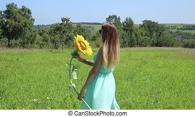 young girl spinning on a green grass, holding sunflower.