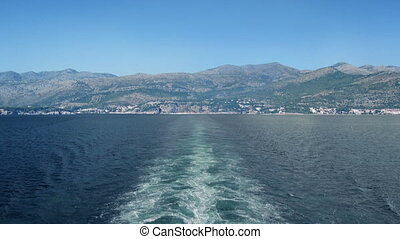Sailing Away From Shore On Sunny Day - View from back of...