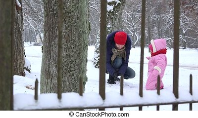 mother play with little baby daughter with snow in winter....