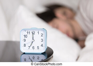 Young couple sleeping in bed next to an alarm clock - Man...