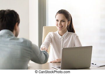 Friendly young businesswoman shaking hands with client,...
