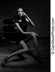 Sexy slim model sitting in fashion armchair and posing in black dress, high heels on dark shadow background. Black and white contrast art portrait