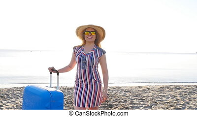 Happy young woman on vacation with a suitcase showing thumbs...