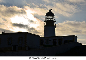 Neist Point Lighthouse Silhouetted Against Cloudy Skies at...