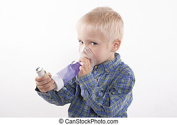 boy with asthma inhaler - young boy using an asthma inhaler,...