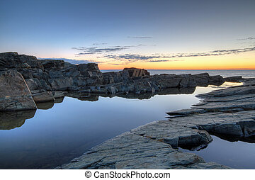 Newoundland Coastline at Sunrise - Rocks and water along the...