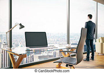 Man in office - Side view of young man looking out of window...