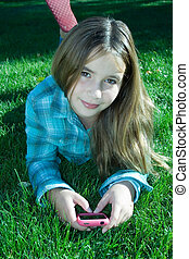 Pretty girl with cell phone laying - Pretty young girl...