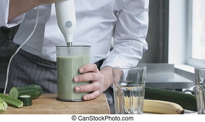Young cook in uniform preparing vegetable smoothie